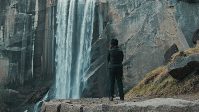 A woman hiker is standing in front of a waterfall thumbnail
