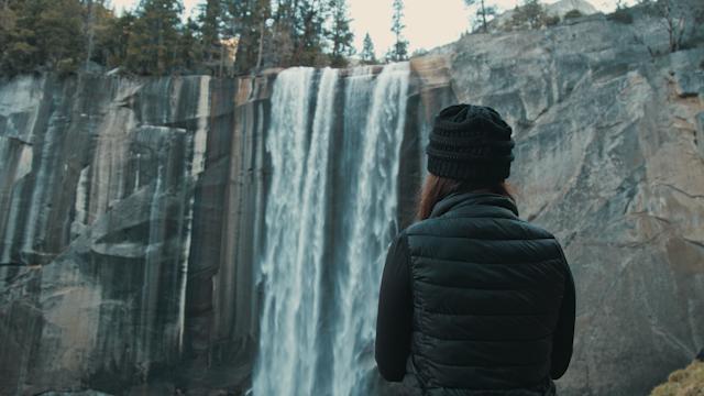A woman hiker is looking at a waterfall thumbnail