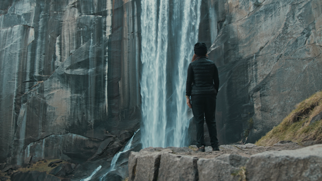 A hiker is standing and looking at a waterfall thumbnail