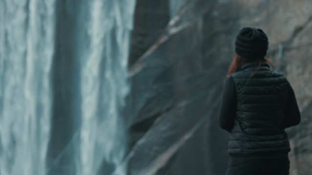 A woman is standing and looking at a waterfall thumbnail