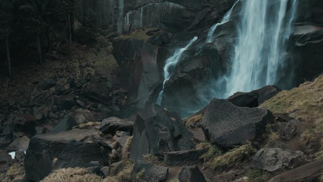 A waterfall flows down a rocky mountain side thumbnail