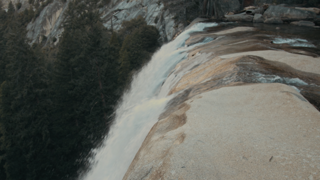 A waterfall flows down into a rocky river bed thumbnail