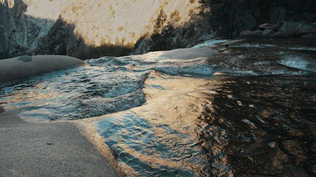 A waterfall is flowing over a rocky cliff thumbnail