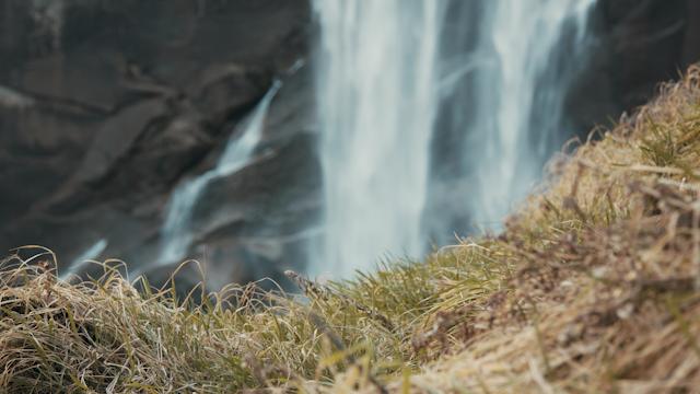 A waterfall flows behind a grassy terrain thumbnail