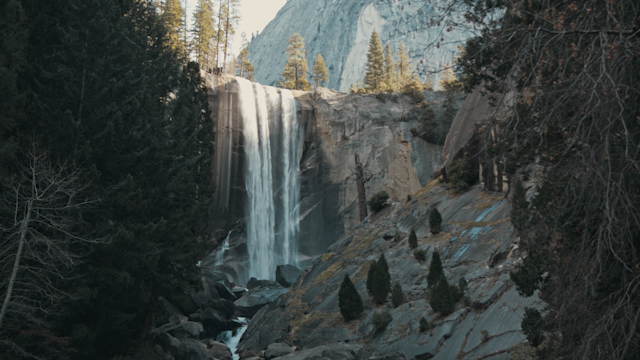 A waterfall flows over a rocky cliff surrounded by trees thumbnail