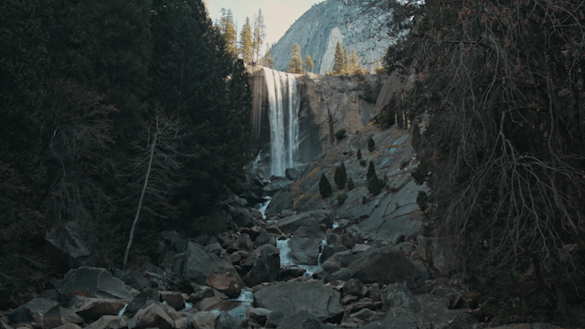 A waterfall flows over a rocky cliff into a rocky river bed through trees thumbnail