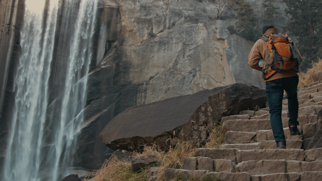 A hiker climbs up rocky stairs toward a waterfall thumbnail