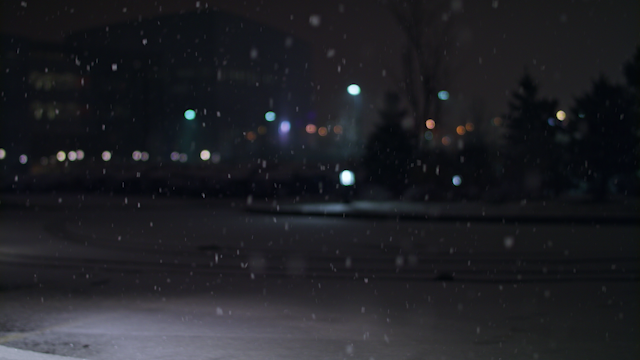 Snow is falling on a dark night with city lights thumbnail