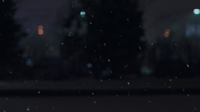 Snow is falling at night with colored lights thumbnail