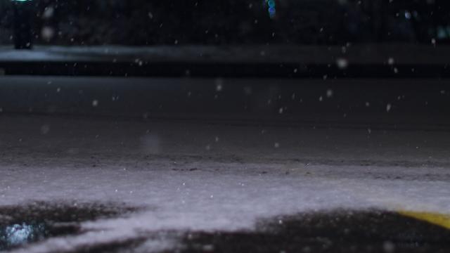 A man walks along a snowy street thumbnail