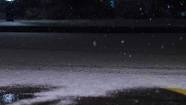 Snow falls on a street at night thumbnail