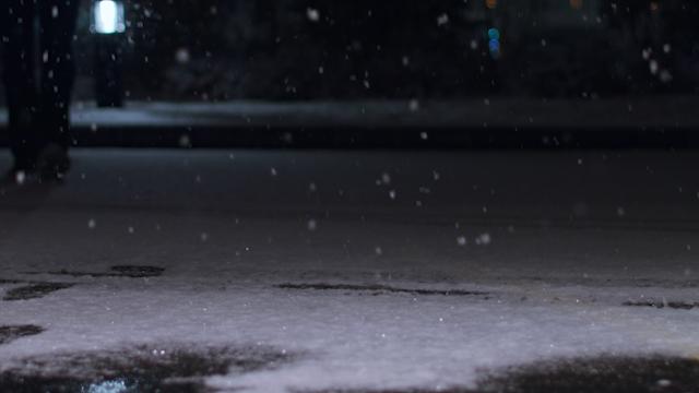 A man is walking down a snowy street at night thumbnail
