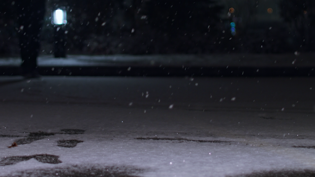 A man walks along a snow filled street at night thumbnail