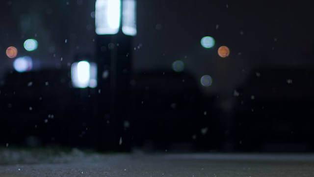 Snow falls to the ground in front of glowing lights thumbnail