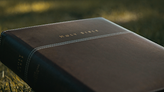 A brown bible is slowly opened to the title page thumbnail