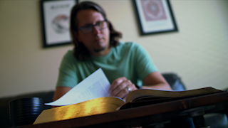 A man is reading a bible in a room thumbnail