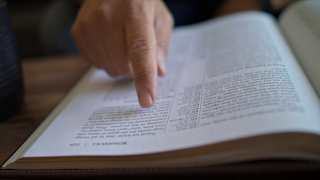 A man is pointing to text on a page of the bible thumbnail