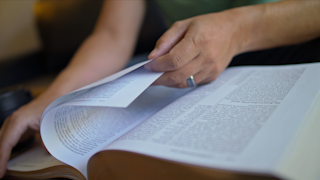 A man is sitting and flipping through pages of the bible thumbnail