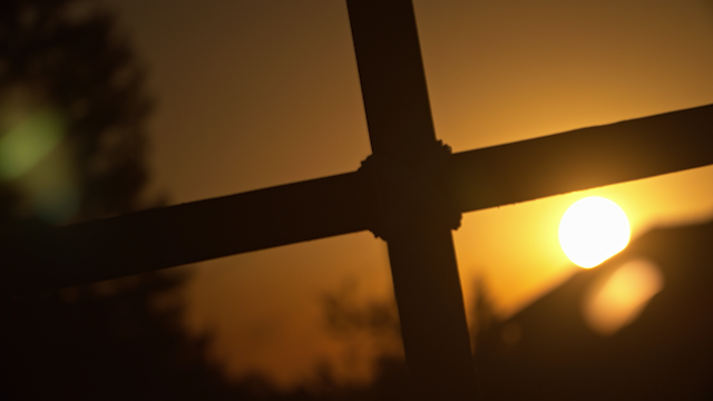 A wooden cross is silhouetted by the sun thumbnail