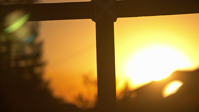 A wooden cross is silhouetted by the sunset thumbnail