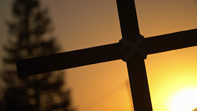 The sun is silhouetting a wooden cross thumbnail