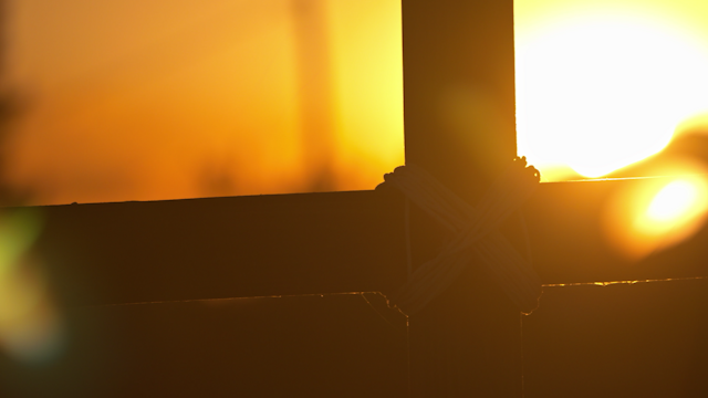 Sun rays shine past a wooden cross at sunset thumbnail