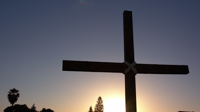 A wooden cross against a sunset sky thumbnail