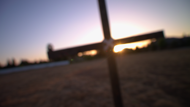 Sunrays shine from behind a wooden cross thumbnail