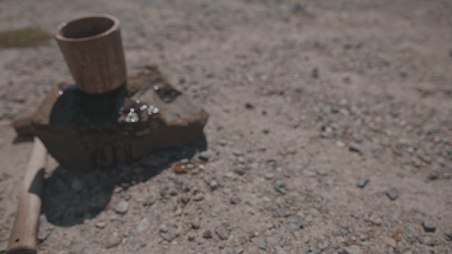 A hammer lays next to a rock with a cup of wine thumbnail