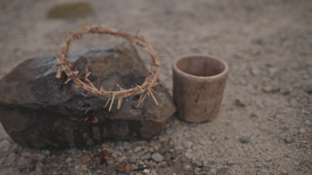 A crown of thorns on a rock next to a cup of wine thumbnail