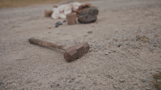 A hammer, wine cup, rocks and clothes are on the ground thumbnail