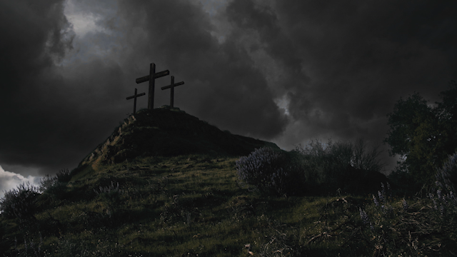 Three crosses are on top of a hill under a dark cloudy sky thumbnail