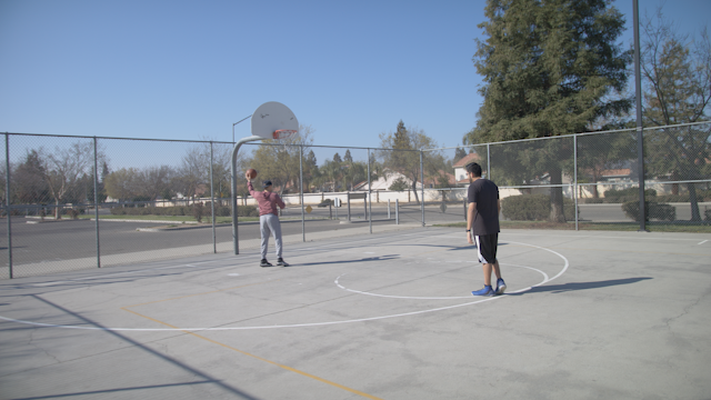 Two friends are shooting hoops on a basketball court thumbnail