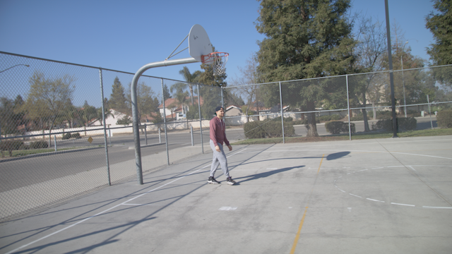 Two friends shoot hoops on a basketball court thumbnail