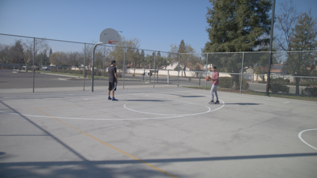 Friends are shooting hoops on a basketball court thumbnail