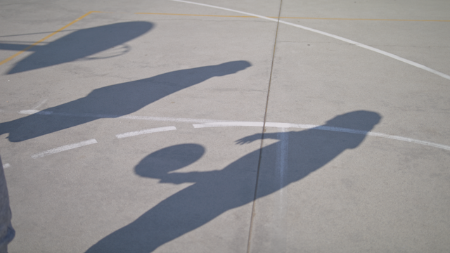 The shadows of two friends on a basketball court thumbnail