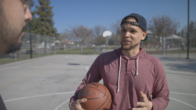 A man smiles and plays with a basketball thumbnail