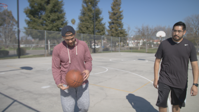 Two men talk as they leave a basketball court thumbnail