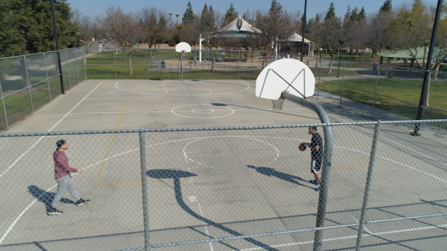 Two men play basketball in a public park thumbnail
