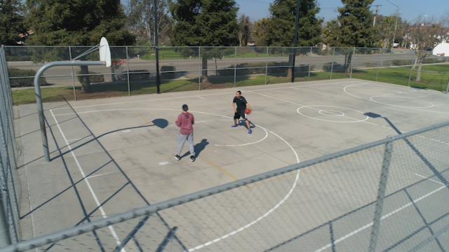 Two men shoot hoops on a public basketball court thumbnail
