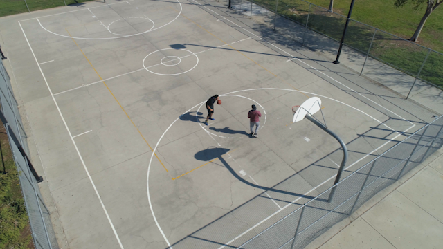 Two men are shooting hoops on a public basketball court thumbnail