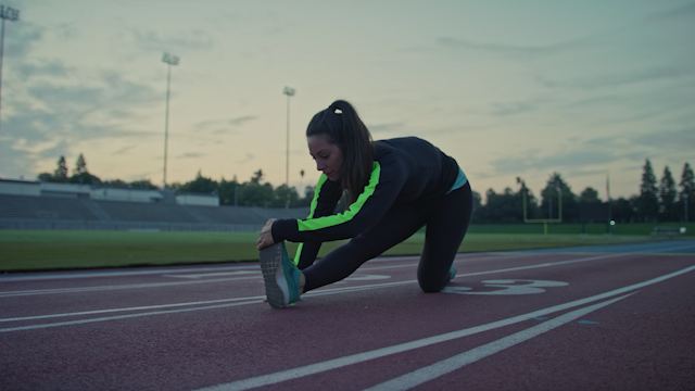 A woman does stretches on a track in the morning thumbnail