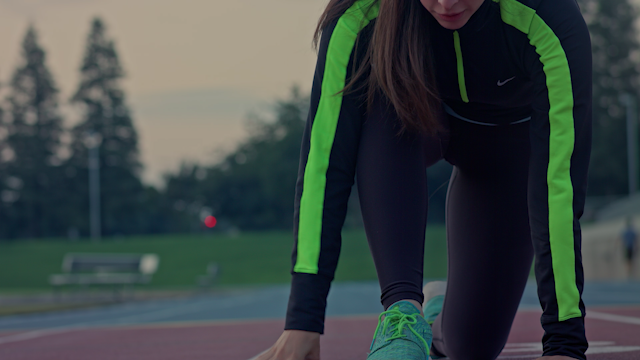 A runner stretches her legs in the morning on a track thumbnail