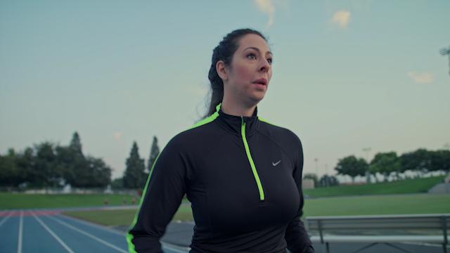 A runner runs down a track in a stadium thumbnail