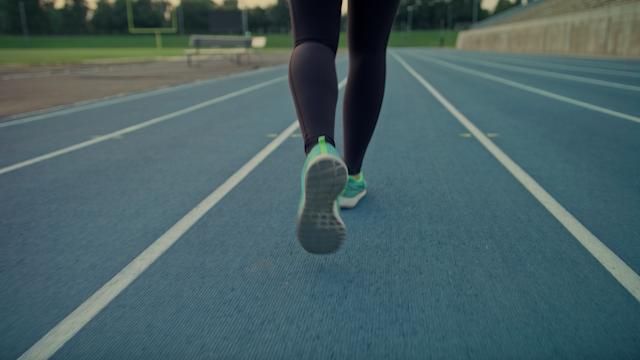 A runner jogs down a track in a stadium thumbnail