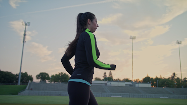 A woman is running on a track in a football stadium thumbnail