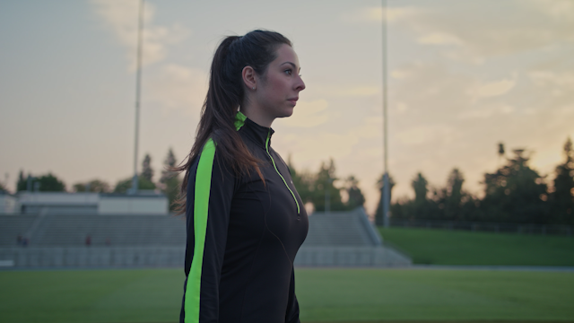 A woman is doing leg stretches on a stadium track thumbnail
