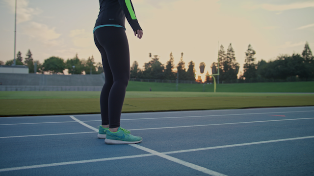 A woman is doing warm up stretches on a track thumbnail
