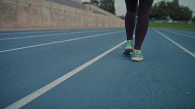 A runner is walking on a track in a stadium thumbnail