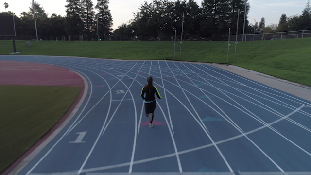 A runner is running around a track in a stadium thumbnail